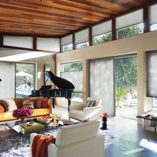 サクラメントのミッドセンチュリースタイルのおしゃれなリビング (ミュージックルーム、ベージュの壁、コンクリートの床、暖炉なし、グレーの床) の写真