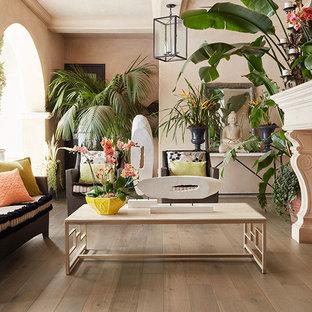 Immagine di un soggiorno tropicale di medie dimensioni e chiuso con sala formale, pareti beige, parquet chiaro, camino classico, cornice del camino in pietra e nessuna TV