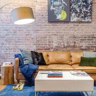 Diseño de salón cerrado, industrial, de tamaño medio, sin chimenea, con paredes rojas, suelo de madera en tonos medios y televisor colgado en la pared