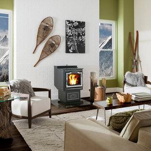 Diseño de salón para visitas cerrado, ecléctico, de tamaño medio, sin televisor, con paredes verdes, suelo de madera oscura, estufa de leña, marco de chimenea de metal y suelo marrón