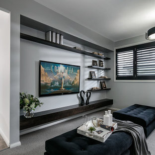Design ideas for a mid-sized contemporary enclosed living room in Other with grey walls, carpet, a wall-mounted tv and grey floor.
