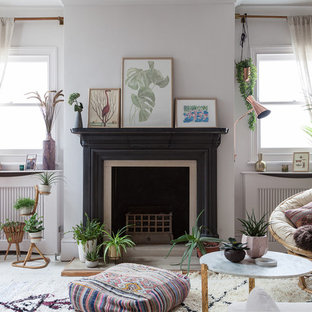 This is an example of a medium sized eclectic open plan living room in London with white walls, painted wood flooring, a standard fireplace, no tv and white floors.