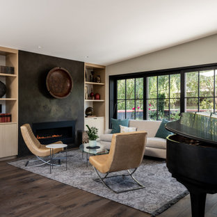 Example of a mid-sized trendy open concept dark wood floor living room design in Seattle with gray walls, a standard fireplace and a concrete fireplace