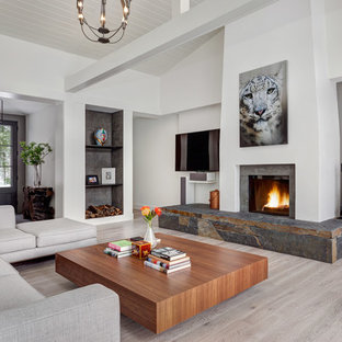 Example of a mid-sized trendy open concept light wood floor and gray floor living room design in Bridgeport with white walls, a standard fireplace, a stone fireplace and a wall-mounted tv