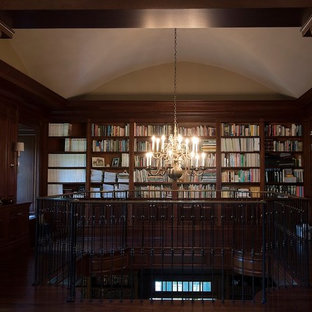 This is an example of a large classic enclosed living room in New York with a reading nook, brown walls, dark hardwood flooring, a standard fireplace, a concrete fireplace surround and no tv.