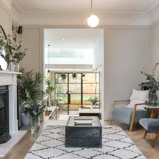 Foto de salón abierto, nórdico, grande, con paredes blancas, suelo de madera en tonos medios, chimenea tradicional y marco de chimenea de piedra