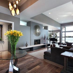 Foto di un grande soggiorno contemporaneo aperto con pareti grigie, nessuna TV, pavimento in legno massello medio, camino classico e cornice del camino in pietra