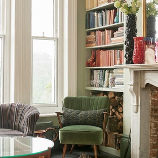 Photo of a mid-sized shabby-chic style formal enclosed living room in Sussex with green walls, painted wood floors, a hanging fireplace, a concealed tv and a stone fireplace surround.