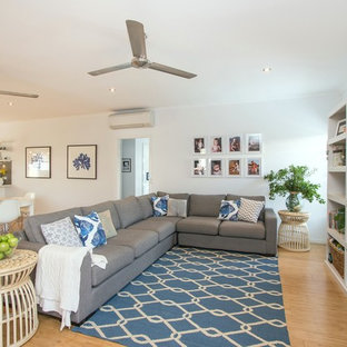 Medium sized coastal open plan living room in Dunedin with white walls, bamboo flooring, no fireplace and a built-in media unit.