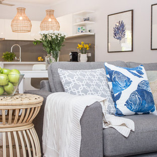 Example of a mid-sized coastal open concept living room design in Dunedin with white walls and a media wall