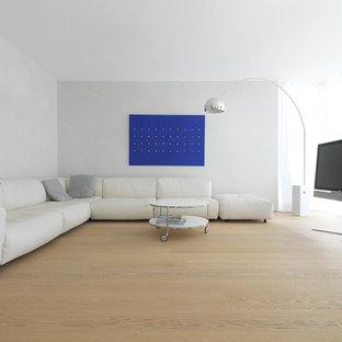 Mittelgroßes Modernes Wohnzimmer ohne Kamin mit weißer Wandfarbe, braunem Holzboden und freistehendem TV in Sonstige