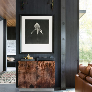 Trendy concrete floor and gray floor living room photo in San Francisco with black walls and a bar