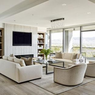 Modelo de salón abierto, actual, grande, con paredes blancas, suelo de madera clara, chimenea lineal, marco de chimenea de baldosas y/o azulejos, pared multimedia y suelo beige