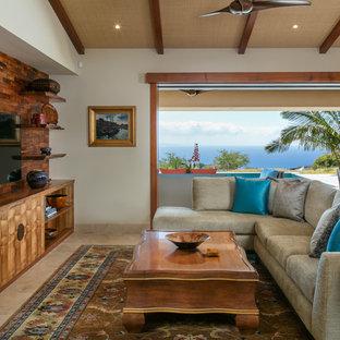 ハワイのトロピカルスタイルのおしゃれな独立型リビング (壁掛け型テレビ、ベージュの床、ベージュの壁、セラミックタイルの床、暖炉なし) の写真