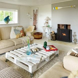 Diseño de salón para visitas cerrado, marinero, de tamaño medio, con paredes blancas, suelo de madera pintada, estufa de leña, marco de chimenea de ladrillo y suelo beige