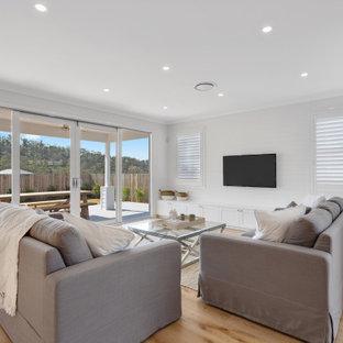 ブリスベンの広いビーチスタイルのおしゃれなLDK (白い壁、淡色無垢フローリング、暖炉なし、壁掛け型テレビ、黄色い床、塗装板張りの壁) の写真