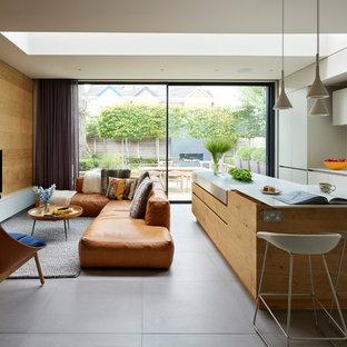 Imagen de salón abierto, actual, con paredes marrones, televisor independiente y suelo gris