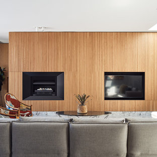Modelo de salón abierto, contemporáneo, grande, con suelo de piedra caliza, chimenea tradicional, marco de chimenea de metal, pared multimedia, suelo gris y paredes grises