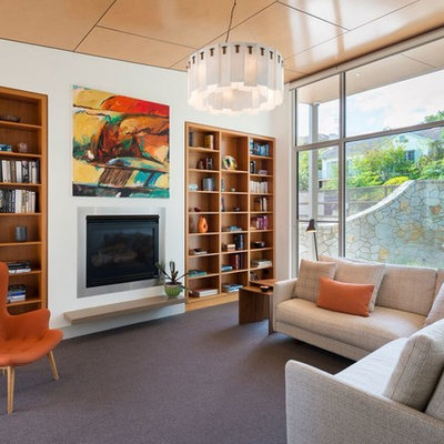 Mid-sized mid-century modern open concept carpeted and gray floor living room library photo in Melbourne with a standard fireplace, a plaster fireplace, white walls and no tv