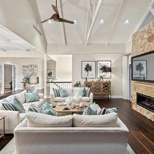 ブリスベンの大きいビーチスタイルのおしゃれなLDK (ベージュの壁、濃色無垢フローリング、石材の暖炉まわり、壁掛け型テレビ、茶色い床、横長型暖炉) の写真