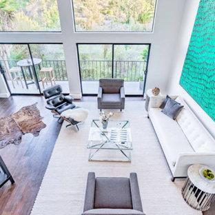 オレンジカウンティの中サイズのコンテンポラリースタイルのおしゃれなリビングロフト (白い壁、茶色い床、無垢フローリング) の写真