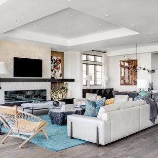 Cette image montre un salon design ouvert avec un mur blanc, un sol en bois foncé, une cheminée ribbon, un manteau de cheminée en pierre de parement, un téléviseur fixé au mur, un sol marron et un plafond décaissé.