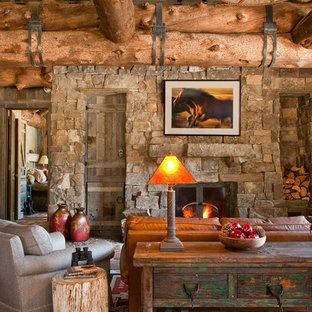 Mountain style dark wood floor living room photo in Other with a standard fireplace and a stone fireplace