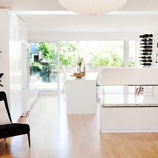 Modelo de salón con barra de bar abierto, minimalista, pequeño, sin televisor, con paredes blancas, suelo de madera clara y chimenea de doble cara