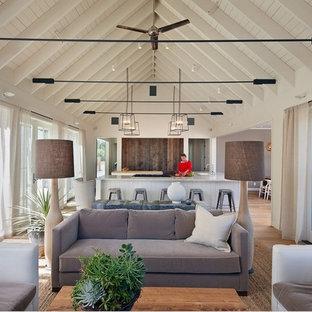 Idée de décoration pour un salon champêtre ouvert avec un mur blanc et un sol en bois brun.