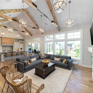 Modelo de salón abierto y abovedado, campestre, con paredes grises, suelo de madera clara, chimenea tradicional, marco de chimenea de ladrillo y suelo marrón