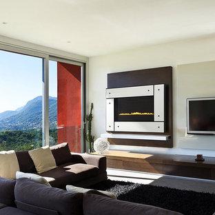 Foto de salón para visitas cerrado, minimalista, pequeño, con paredes beige, suelo de travertino, chimenea tradicional, marco de chimenea de metal, televisor colgado en la pared y suelo beige