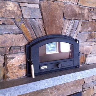 Ejemplo de salón actual con estufa de leña y marco de chimenea de piedra