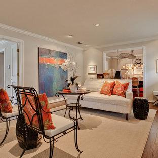 Abgetrenntes, Mittelgroßes, Fernseherloses Klassisches Wohnzimmer mit beiger Wandfarbe, dunklem Holzboden, Kamin und Kaminsims aus Stein in Dallas
