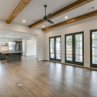 ヒューストンのトランジショナルスタイルのおしゃれなLDK (白い壁、標準型暖炉、木材の暖炉まわり、壁掛け型テレビ、白い床) の写真