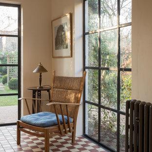 Immagine di un soggiorno bohémian di medie dimensioni con libreria, pareti bianche, pavimento con piastrelle in ceramica e pavimento multicolore