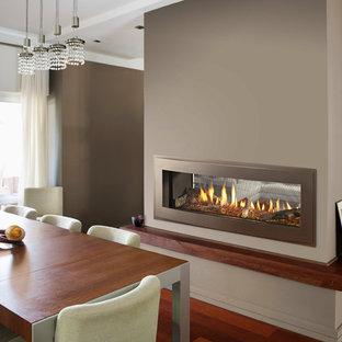 Foto de salón moderno, de tamaño medio, con paredes marrones, suelo de madera en tonos medios, chimenea de doble cara, marco de chimenea de metal y suelo marrón