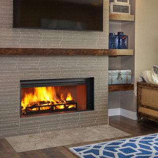 Modelo de salón abierto, moderno, de tamaño medio, con paredes marrones, suelo de madera en tonos medios, chimenea lineal, marco de chimenea de baldosas y/o azulejos, televisor colgado en la pared y suelo marrón