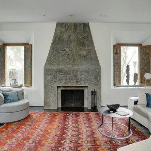 ヒューストンのサンタフェスタイルのおしゃれなリビング (白い壁、コンクリートの床、標準型暖炉、コンクリートの暖炉まわり) の写真
