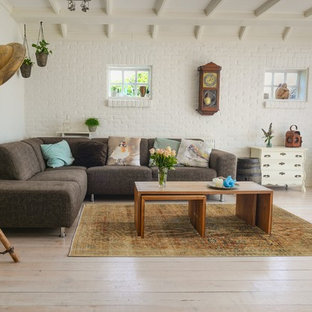 Photo of a medium sized farmhouse enclosed living room in Stockholm with white walls, painted wood flooring and white floors.