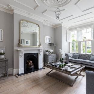 Idee per un grande soggiorno tradizionale chiuso con pareti grigie, parquet chiaro, camino classico, cornice del camino in metallo, nessuna TV e pavimento marrone