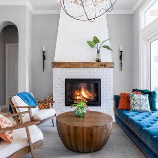 Идея дизайна: открытая гостиная комната в морском стиле с серыми стенами, стандартным камином и фасадом камина из плитки