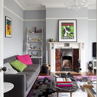 Imagen de salón cerrado, tradicional renovado, de tamaño medio, con chimenea tradicional, paredes azules, suelo de madera oscura y marco de chimenea de baldosas y/o azulejos
