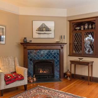 Imagen de salón para visitas cerrado, de estilo americano, de tamaño medio, sin televisor, con paredes beige, suelo de madera en tonos medios, chimenea tradicional, marco de chimenea de baldosas y/o azulejos y suelo naranja