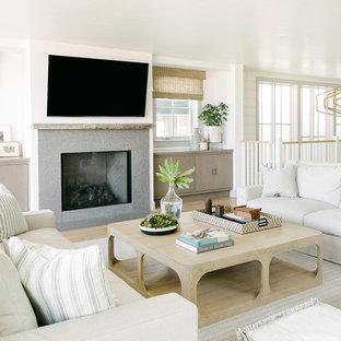 ロサンゼルスのビーチスタイルのおしゃれなリビングロフト (白い壁、淡色無垢フローリング、標準型暖炉、石材の暖炉まわり、壁掛け型テレビ) の写真