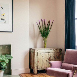 Scandi living room in London with pink walls and medium hardwood flooring.