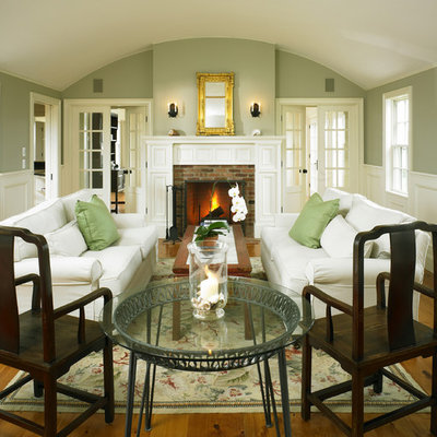 Example of a small country enclosed medium tone wood floor living room design in Boston with green walls, a standard fireplace and a brick fireplace