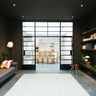 Idee per un ampio soggiorno industriale aperto con pareti nere, libreria e pavimento in cemento