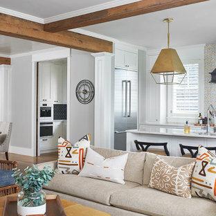 グランドラピッズの中くらいのビーチスタイルのおしゃれなLDK (グレーの壁、無垢フローリング、標準型暖炉、石材の暖炉まわり、壁掛け型テレビ、茶色い床) の写真
