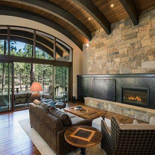 Modelo de salón abierto, rural, con paredes multicolor, suelo de madera en tonos medios, chimenea lineal, marco de chimenea de metal, televisor retractable y suelo marrón