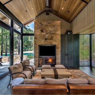 Inspiration pour un grand salon chalet en bois ouvert avec un mur beige, un sol en bois brun, une cheminée standard, un manteau de cheminée en pierre, un téléviseur fixé au mur, un sol marron et un plafond en bois.